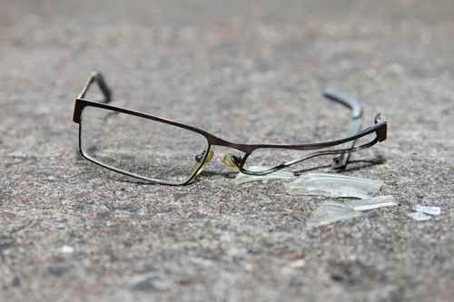 broken eyeglasses on concrete