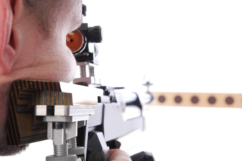 Marksman sighting down the barrel of an air rifle